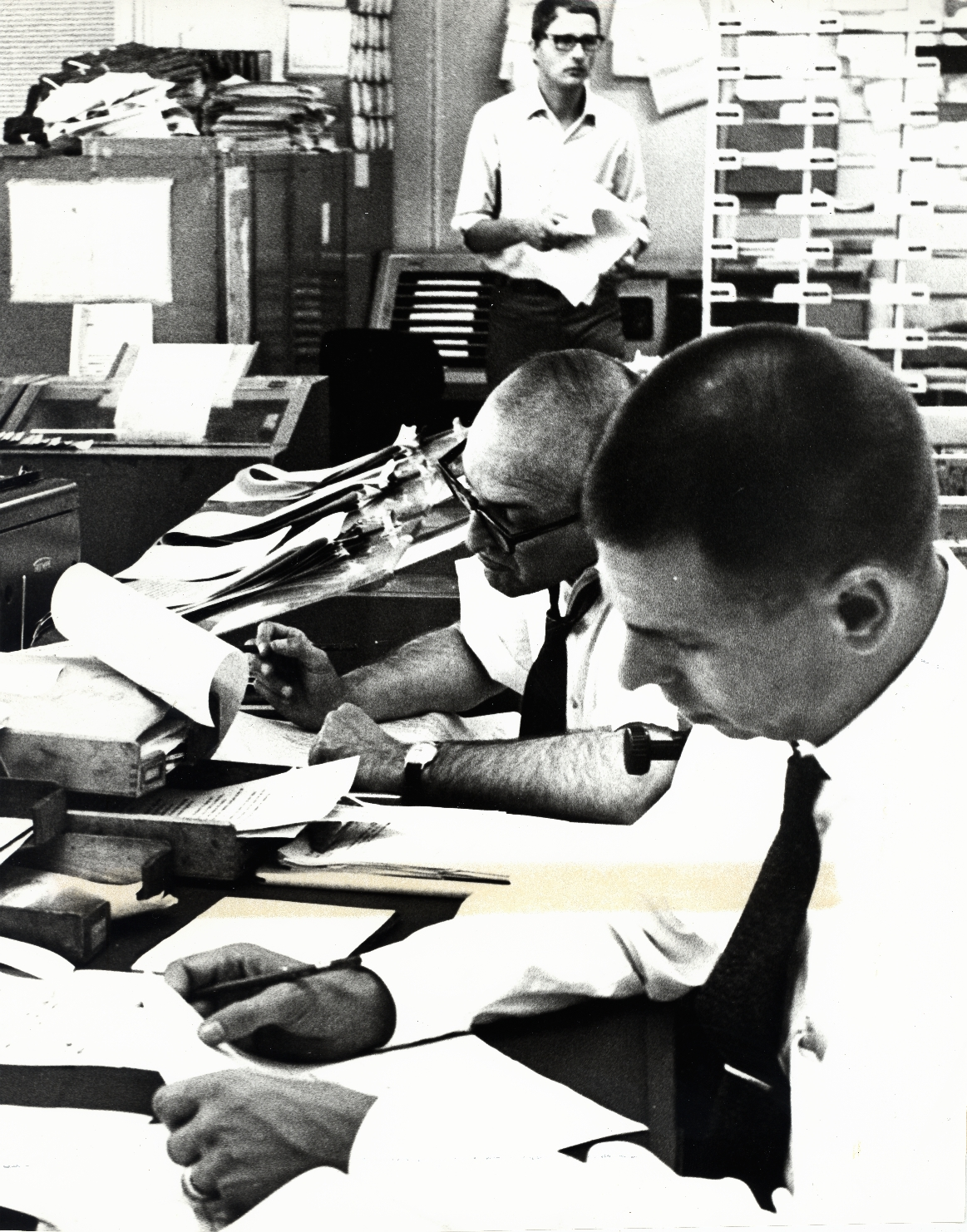 RFE COVERS THE MIDDLE EAST CRISIS -- In the Central News Room of Radio Free Europe headquarters in Munich, Germany, RFE editors examine latest dispatches on the Arab-Israeli war. RFE kept its 22 listeners in East Europe informed with up-to-the-minute bulletins on developments in the conflict. June 1967.